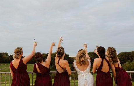 bride and her bridesmaids cheers-ing the sky at a golf course wedding